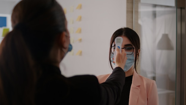 体温計で体温計を使って体温を測定している女性のクローズアップ19.コロナウイルスの世界的な大流行の間、職場で保護フェイスマスクを着用して社会的距離を保つ同僚