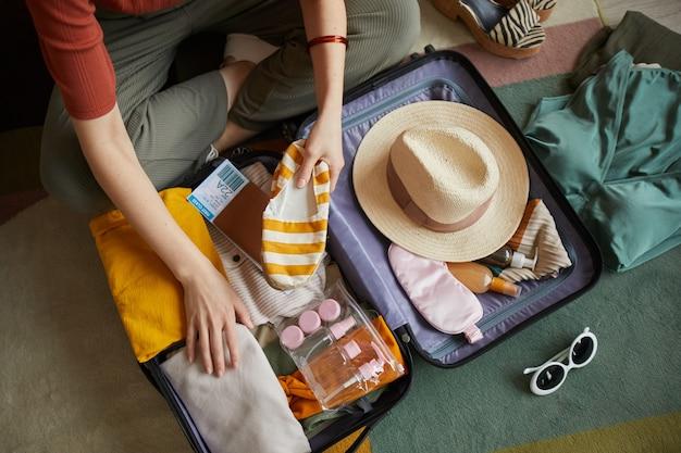 彼女は夏休みに行くスーツケースに彼女の服を詰める女性のクローズアップ