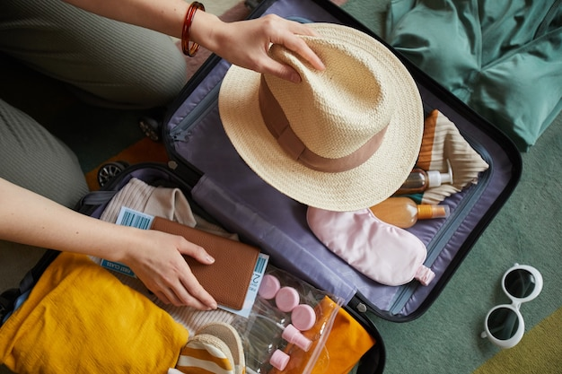 彼女が休暇に行くスーツケースに彼女の服を詰める女性のクローズアップ
