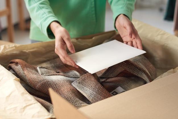 Крупным планом женщина упаковывает новую одежду в коробку и кладет на нее открытку перед доставкой
