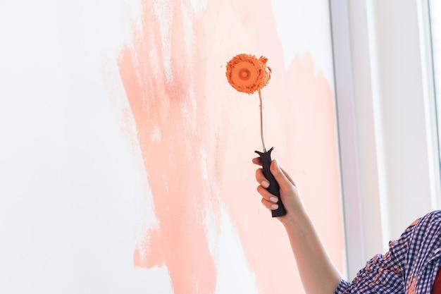 그녀의 새 아파트에서 여자 그림 벽을 닫습니다. 리노베이션 및 재장식 개념입니다.