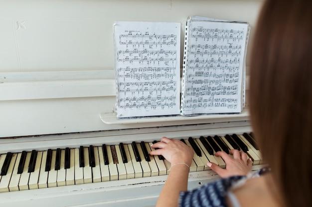 Крупным планом женщина играет на пианино, глядя на музыкальный лист на фортепиано