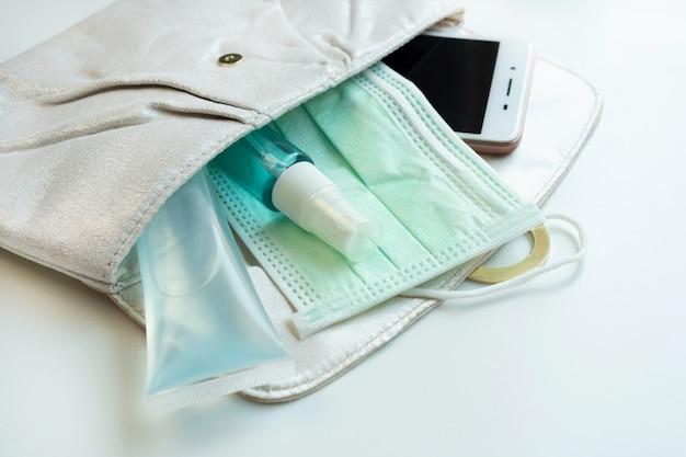 スマートフォン、消毒剤、アルコールスプレー、防護マスクと女性のポーチのクローズアップ。医療コンセプト。