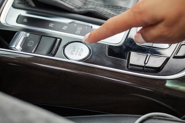 ボタンを押す女性のクローズアップエンジン車を起動します。