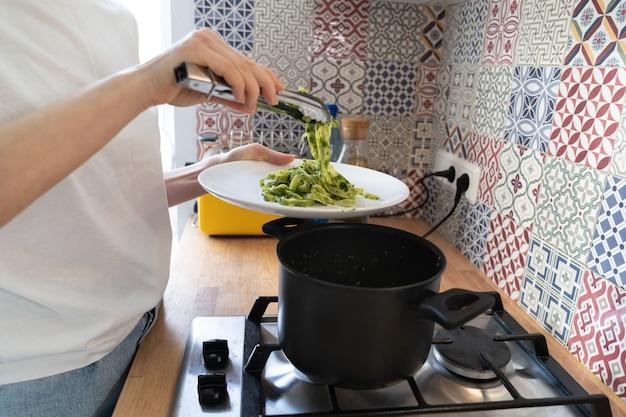 女性のクローズアップは、皿に鍋からフェットチーネペストペーストを置きます。自家製イタリア料理、本物の家庭生活。