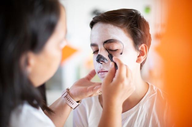 死者の日のお祝いのために10代の少年に化粧をしている女性のクローズアップ。 (死者の日)。 Premium写真