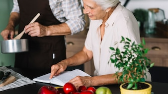 Close-up of woman reading book sitting near the man preparing food in the kitchen