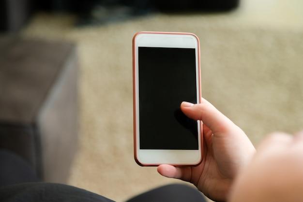 自宅でスマートフォンでニュースを読んでいる女性のクローズアップ。