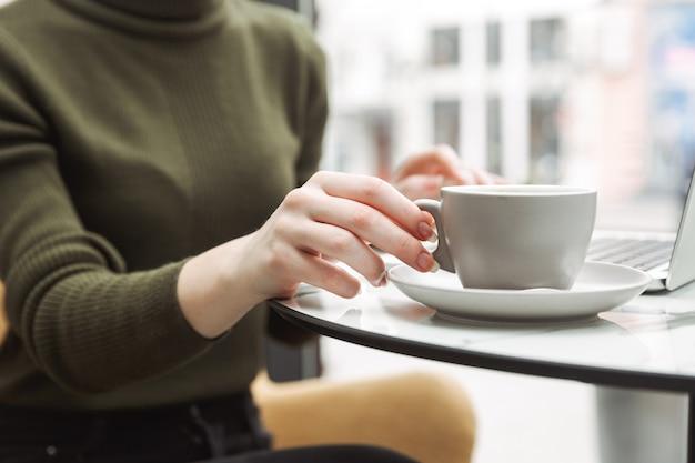 屋内のカフェテーブルでリラックスし、コーヒーを飲みながら女性のクローズアップ