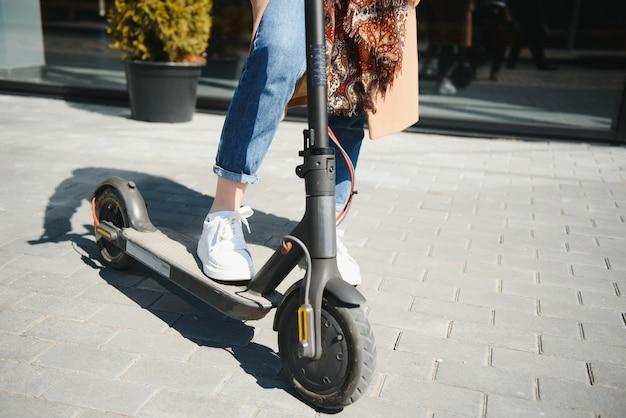 街並み、モーションブラーで黒い電動キックスクーターに乗っている女性のクローズアップ