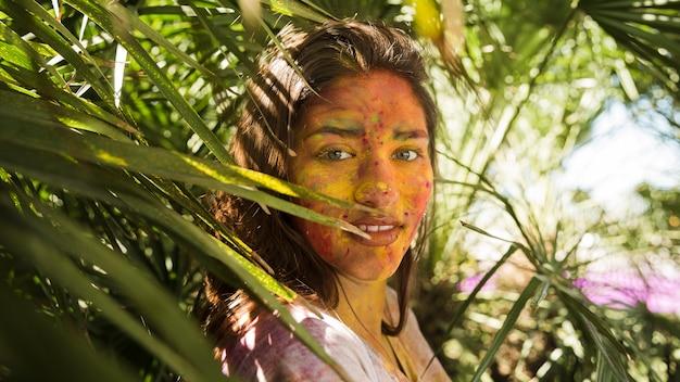 Крупный план женского лица, покрытого порошком цвета холи, стоящего рядом с растениями