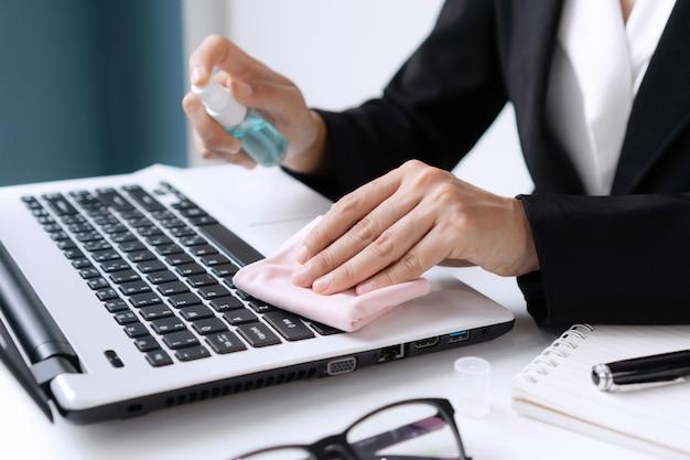 女性の手のクローズアップは、オフィスのワークデスク上のコンピューターにアルコールスプレーを適用します