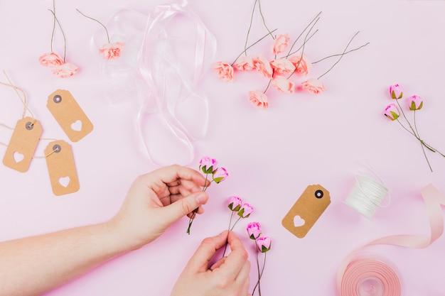 ピンクの背景にリボンとタグで花を生ける女性の手のクローズアップ
