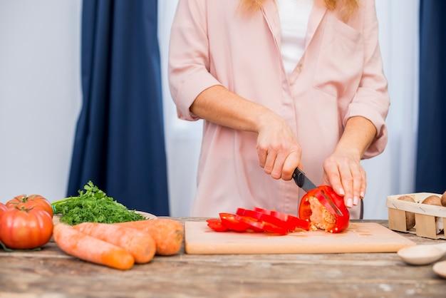 테이블 위에 도마에 칼으로 빨간 피망을 절단하는 여자의 손의 근접