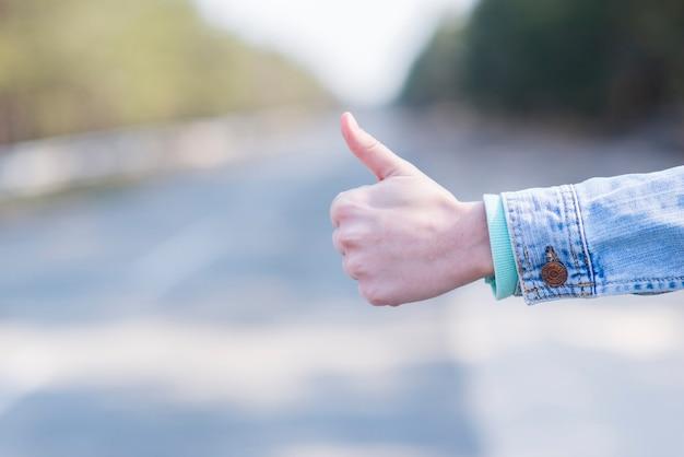 田舎道でヒッチハイクの女性の手のクローズアップ