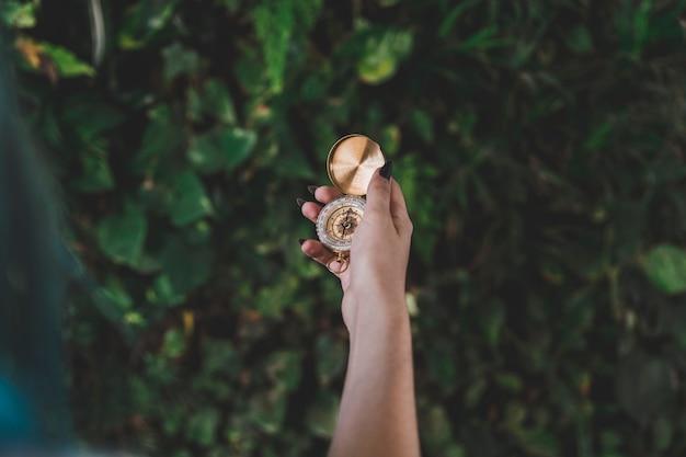 ゴールデンレトロなコンパスを保持している女性の手のクローズアップ