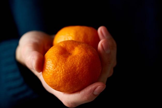 Крупный план женской руки, держащей два целых ярких цитрусовых мандарина