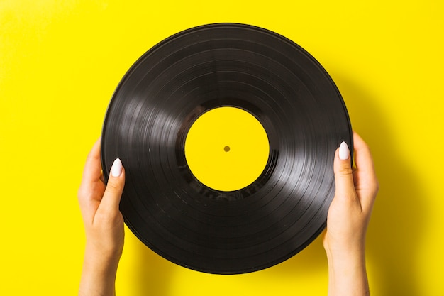 黄色の背景にビニールレコードを持っている女性の手のクローズアップ