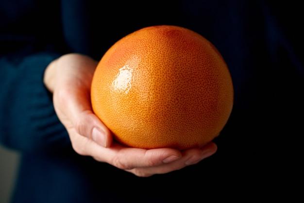 Крупный план женской руки, держащей весь яркий грейпфрут цитрусовых