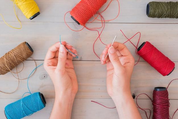 木の机の上の糸と針を持っている女性の手のクローズアップ