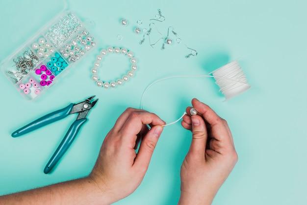 ティールの背景にブレスレットを作るための白い糸に真珠を挿入する女性の手のクローズアップ