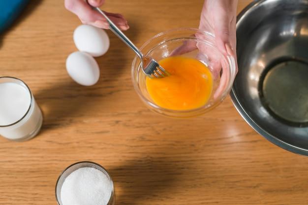 Крупным планом женской руки, смешивая яичный желток с вилкой в стеклянной посуде
