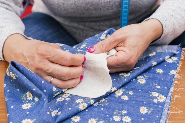 針と糸で花の青い布を縫う女性の手のクローズアップ