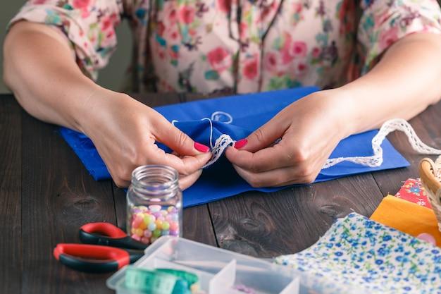 Крупный план женской руки шить лоскутное шитье