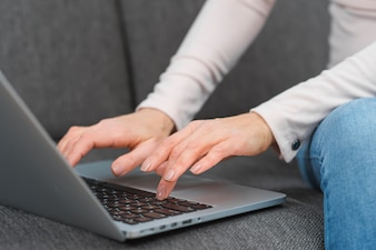 Close-up of woman's hand typing on laptop over the sofa