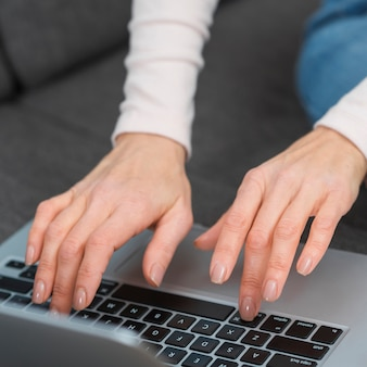 Close-up of woman's hand typing on laptop