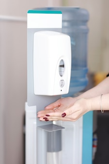병원에서 손을 청소하기 위해 자동 알코올 디스펜서를 사용하여 여성의 손을 닫습니다.