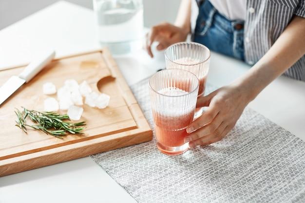 木製の机の上のグレープフルーツデトックスダイエットスムージーローズマリーと氷の部分で女性の手のメガネのクローズアップ。