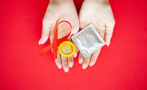 赤いリボンと安全なセックスを求めるコンドームを後ろに持っている女性の手のクローズアップ