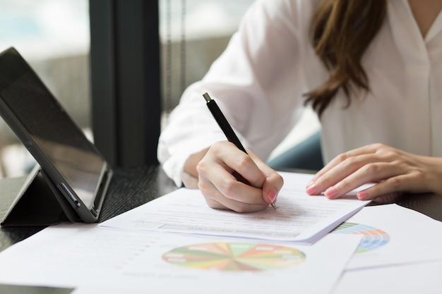 많은 문서와 함께 바탕 화면에 배치 된 메모장에 작성하거나 서명하는 여자의 손을 닫습니다.