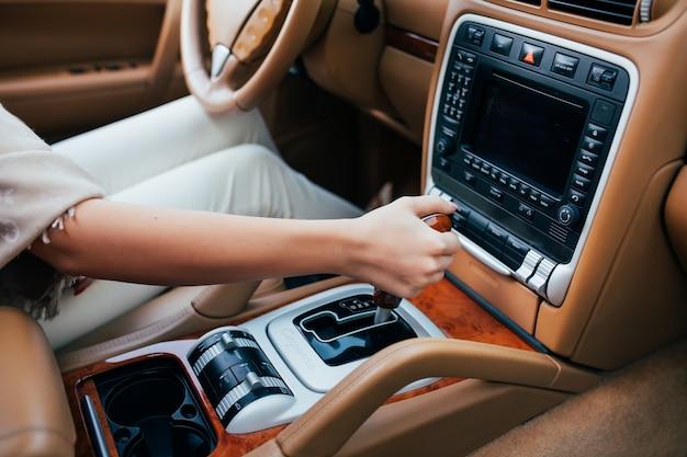 車のギアボックスでギアをシフトする女性のクローズアップ
