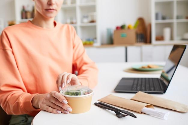 Крупный план женщины, сидящей за столом и открывающей коробку с едой, которая заказывает еду на вынос