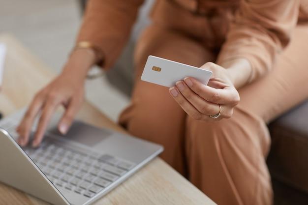 ノートパソコンを使用してテーブルに座って、購入のためにクレジットカードでオンラインで支払う女性のクローズアップ