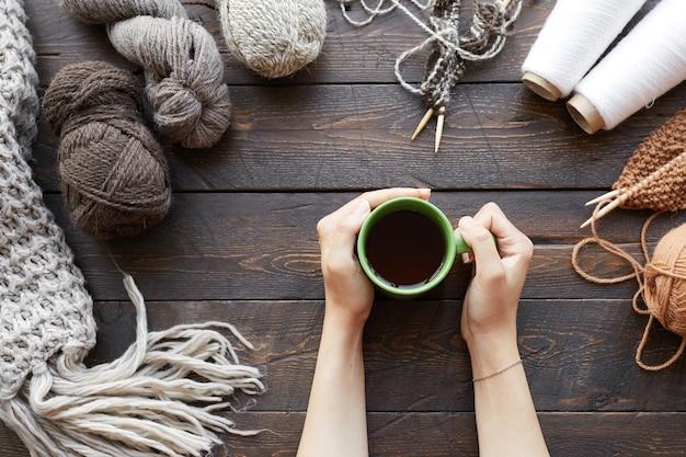 糸のボールと完成したウールの服を着て木製のテーブルに座って、熱いお茶を飲む女性のクローズアップ