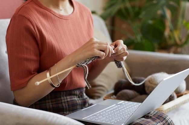 그녀의 무릎에 노트북과 함께 소파에 앉아 집에서 양모 스웨터를 뜨개질 여자의 근접