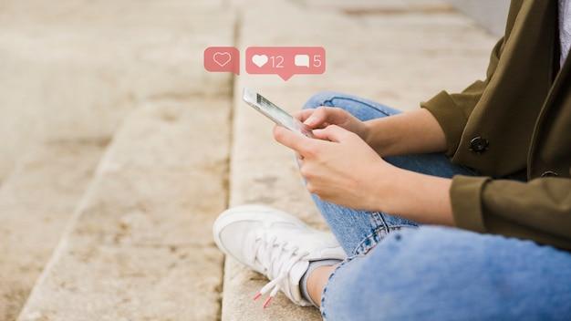 Крупный план женщины, сидящей на лестнице, используя приложение для социальных сетей на мобильном телефоне