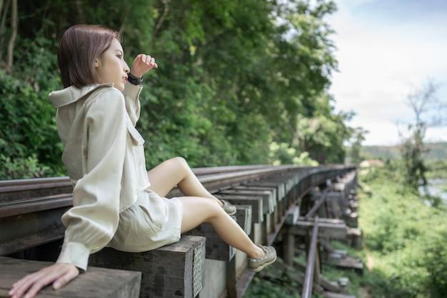 田園風景のヴィンテージ鉄道線路に座っている女性のクローズアップ
