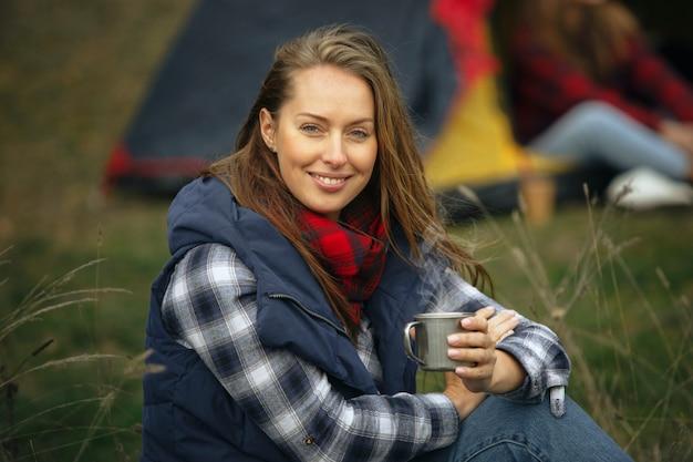 Крупным планом женщина улыбается и пьет чай с группой друзей на фоне кемпинга в лесу.