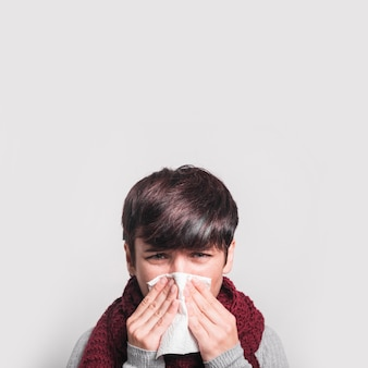 Close-up of woman sneezing with tissue against white background