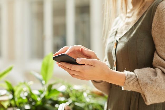 Крупный план женщины, стоящей и печатающей сообщение на своем мобильном телефоне