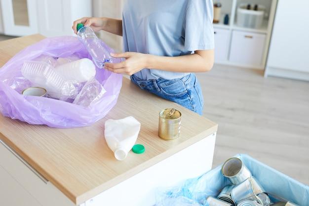 テーブルに立って、自宅でゴミをさまざまなパケットに分類する女性のクローズアップ