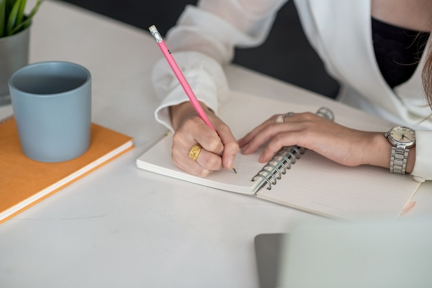 オフィスの机の上でメモを取る女性のクローズアップ