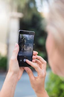 携帯電話で写真を撮っている女性のクローズアップ