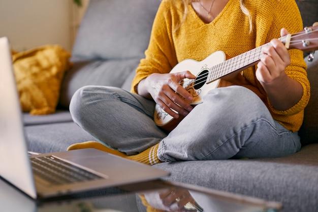 Крупным планом - женщина берет уроки укулеле онлайн со своего ноутбука во время карантина covid.