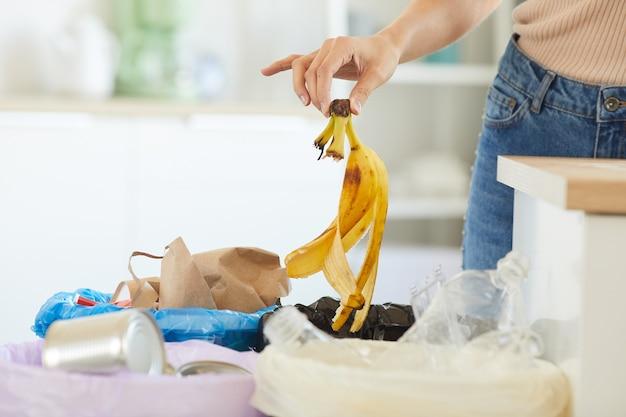 ゴミ箱にバナナの皮を投げる女性のクローズアップ