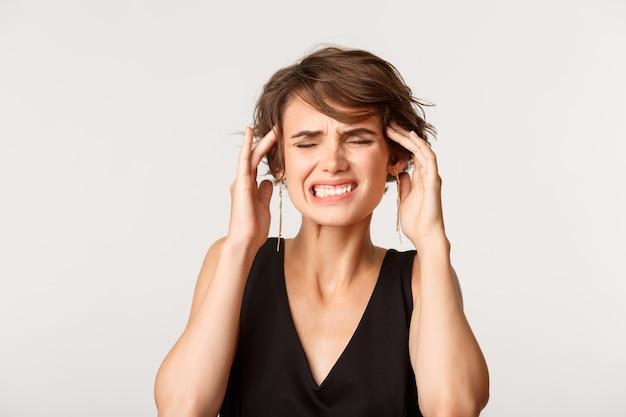 頭に触れて顔をゆがめ、頭痛や片頭痛があり、白の上に立っている女性のクローズアップ。